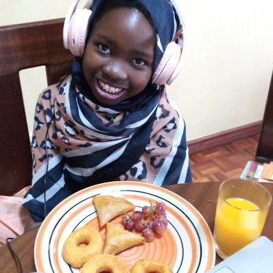 Alesta all dressed up in Swahili clothes enjoying her breakfast..jpeg